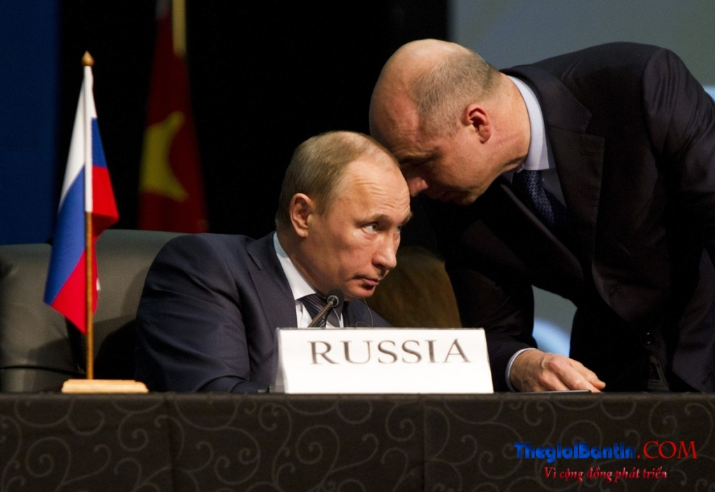 An aide speaks to Russian President Vladimir Putin during closing remarks at the fifth BRICS Summit in Durban
