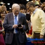 Berkshire Hathaway CEO Warren Buffett gets his wallet out to pay a bet to Microsoft co-founder Bill Gates after participating in a newspaper throwing contest prior to the Berkshire annual meeting in Omaha